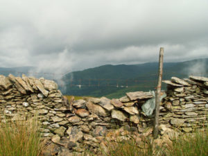 Old stone wall falling down, revealing beautiful mountain scene beyond
