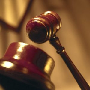 Closeup of a judge's wooden gavel about to strike down