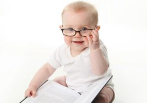 Photo of baby wearing glasses reading a book alone