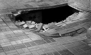 Large hole in a brick sidewalk
